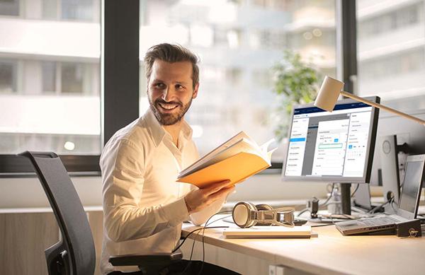 Man smiling at computer desk